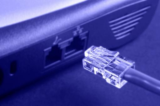 blue-toned glowing ethernet connector with cable approaching socket on laptop